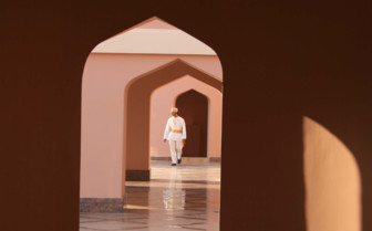 A Man Walking through Arched Doorways in Nizwa