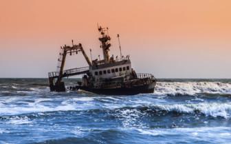 Pink sunset skies and ship wreck at Namibia coast
