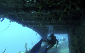 Scuba diver swimming through ship