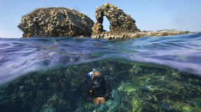 A diver underwater with a perforated rock above the waves behind him