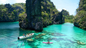 Bright turquoise water and limestone cliffs with two boats